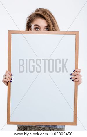 Portrait of a young woman peeping over blank board isolated on a white background