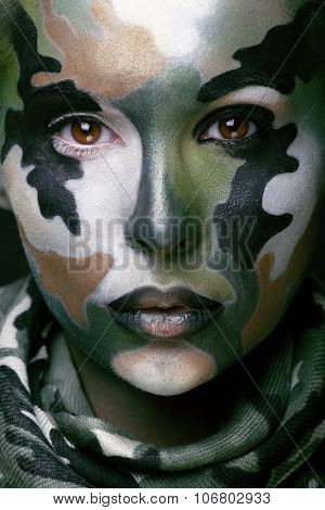 Beautiful young fashion woman with military style clothing and face paint make-up, khaki colors, hal