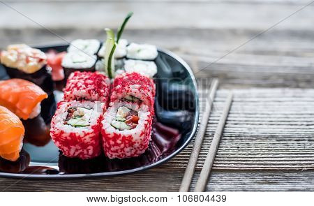 assorted sushi on a plate with chopsticks on wooden table