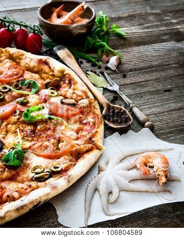 delicious pizza with seafood on wooden table