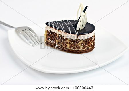 Chocolate cake slice on white dish