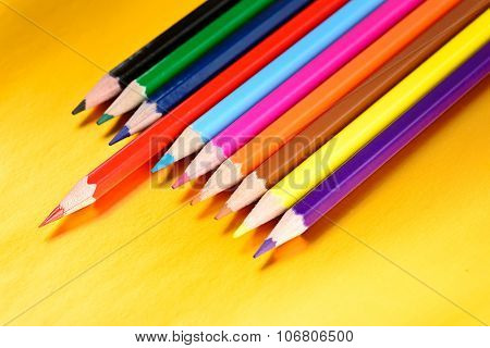 color pencils with different color over golden background