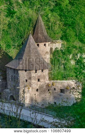 Ancient stone castle  in Kamianets Podilskyi standing on hill with green trees and bushes