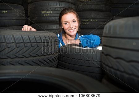 Portrait of a young, pretty, mechanic in a store room, surrounded by tyres with various treads, and purposes