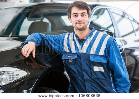 A confident, reliable, trustworthy looking professional mechanic, leaning against a black sedan