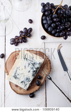 Blue mould, mold cheese with fresh grape. White wooden background