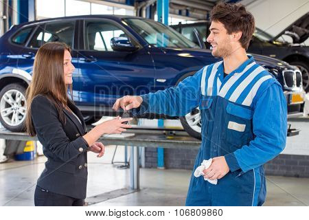 Young, pretty woman, receiving the keys of her new used second hand car from a service mechanic at a car dealer garage