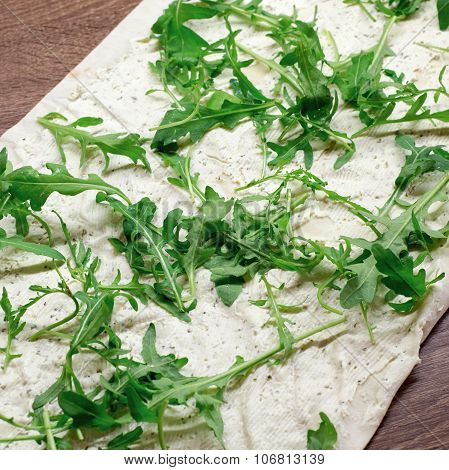 Making lavash rolls with rucola and cheese