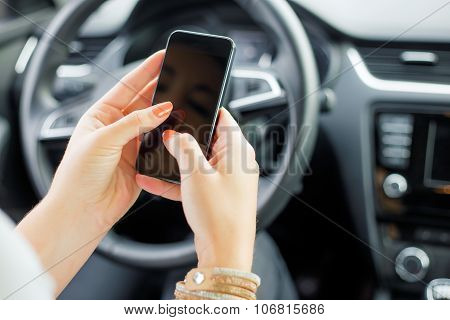 Female sitting in the car and texting