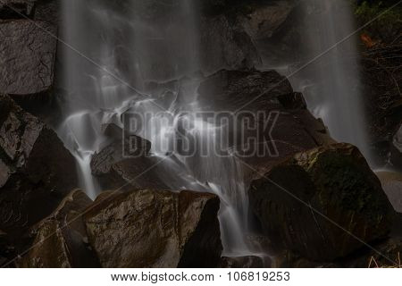 Base Of Waterfall, Water Cascading On Rocks.