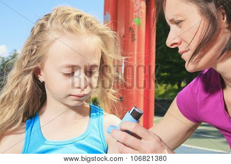 mother using inhaler with her asthmatic daughter