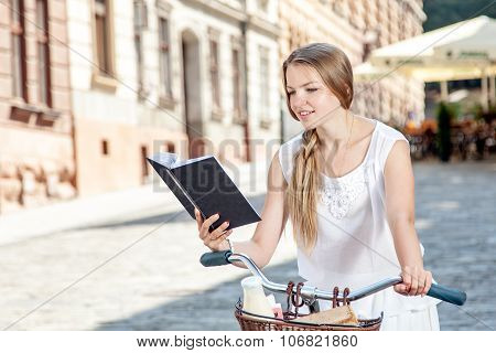 Women On Pink Bicycle With Grocery Basket Reading Book