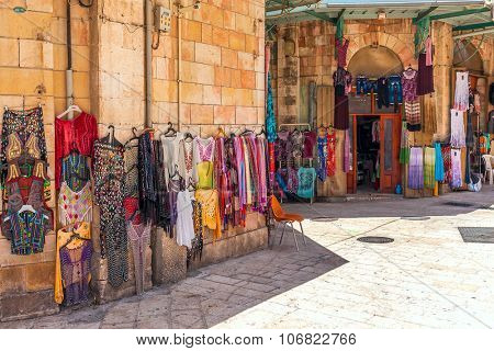 JERUSALEM, ISRAEL - JULY 26, 2015: Colorful clothes and small shop on bazaar - famous market place, popular with tourists and pilgrims visiting Old City of Jerusalem.