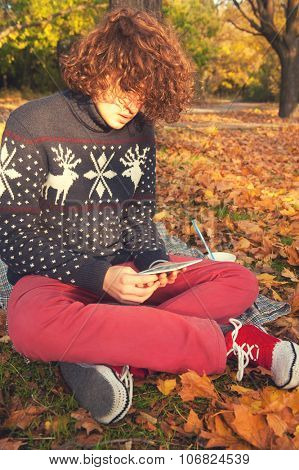 Young adult man dressed in knit sweater with deers, knit shoes and red jeans, have a leisure sitting in autumn park and reading the electronic book.