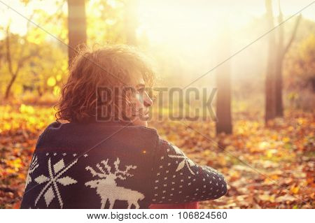 Young adult man dressed in knit sweater with deers sitting  on autumn leaves in a sunset park, backlight.