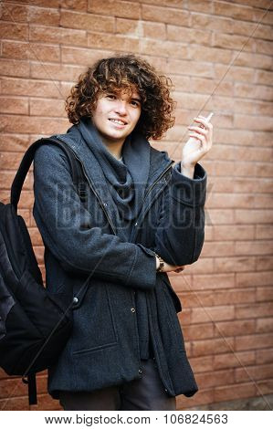 Portrait of a young smiling handsome man with curly hairstyle dressed in gray jacket, standing against brick wall and smoking a cigarette.