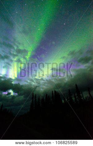 The Aurora Borealis Emerges Through Clouds Remote Alaska