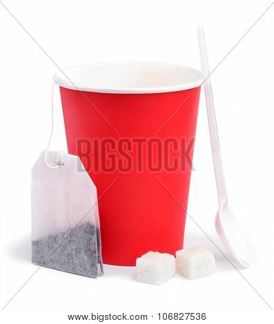 Paper cup, teabag, spoon and sugar.