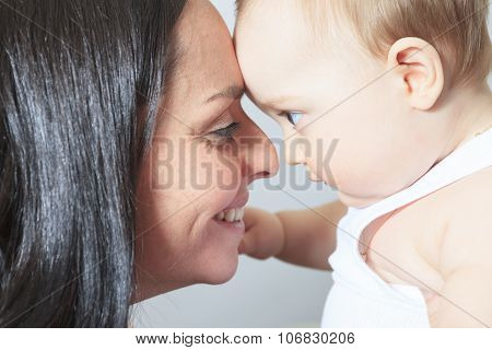 Happy 8 month old baby boy with mother