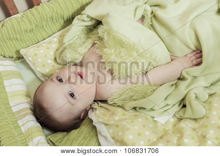 Overhead view of cute baby boy lying under cradle