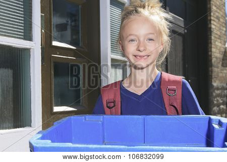 Young girl with recycle bin outside