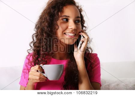 Close up portrait of young woman in pink dress speaking by cellphone with cup of coffee