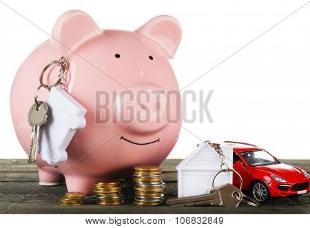 Piggy bank with keys on wooden table, isolated on white