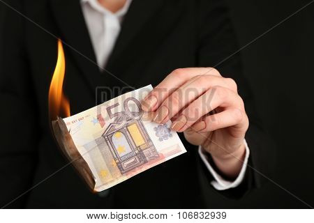 Woman burning Euro banknotes closeup