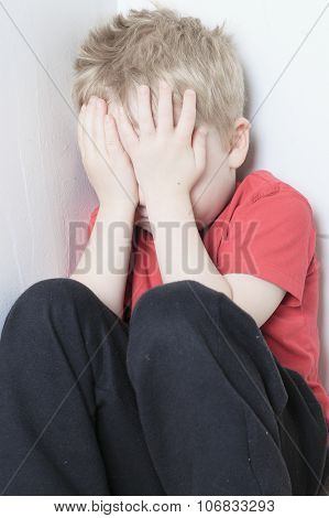 Neglected lonely child leaning at the wall