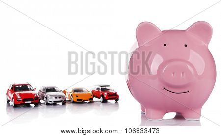 Pig moneybox and toy cars isolated on white