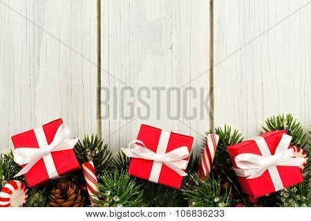 Christmas branches, gifts and candy canes border on white wood