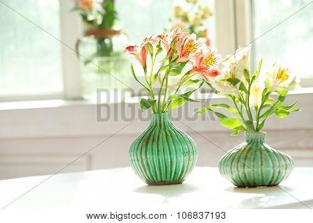 Beautiful Alstroemeria flowers in aquamarine vases on window background