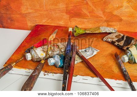 Painting Brush And A Palette Knife On Orange Canvas Desk