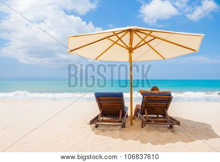 woman resting under umbrella facing the seaside in a deserted beach