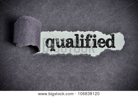 Qualified Word Under Torn Black Sugar Paper