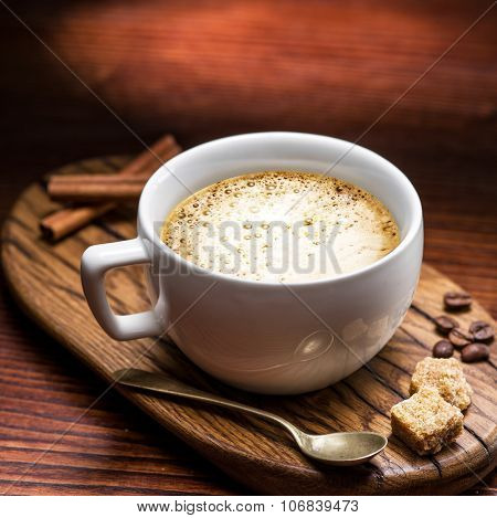 Cup of cappuccino on the aged wooden tray.