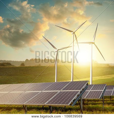 solar panels and wind turbines on sunset summer landscape