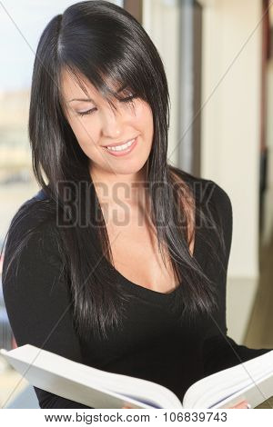 A beautiful confident young female student studying.