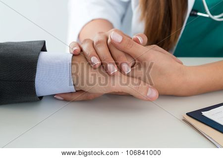 Close-up Of Friendly Female Medicine Doctor's Hand Holding Male Patient's Hand To Support Him