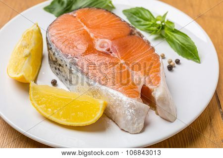 Raw Salmon Steak with Lemons Wedges and Basil Leaves