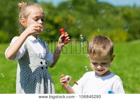 Lovely children blow soap bubbles on a bright sunny day. Brother and sister
