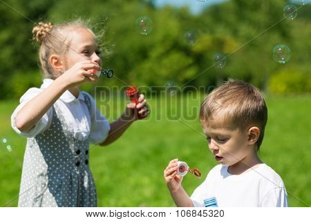 Lovely kids blow bubbles in the park. Brother and sister.