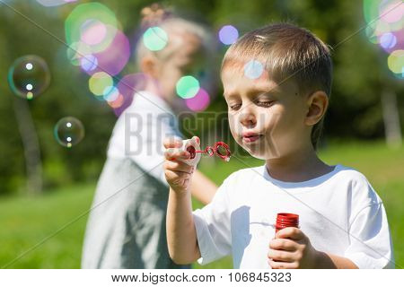 Happy children blow soap bubbles on a bright sunny day. Siblings.
