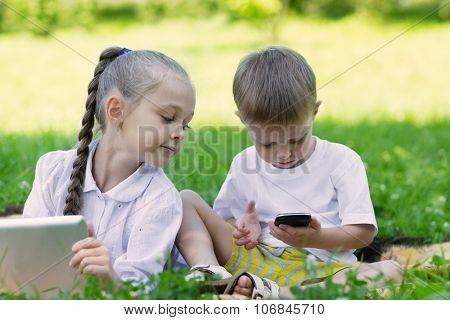 Happy children using tablet PC and smartphone in perk