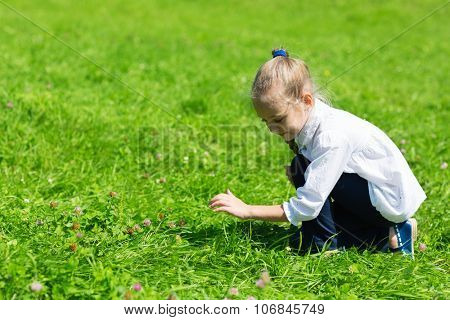 Girl catching a grasshopper in the grass