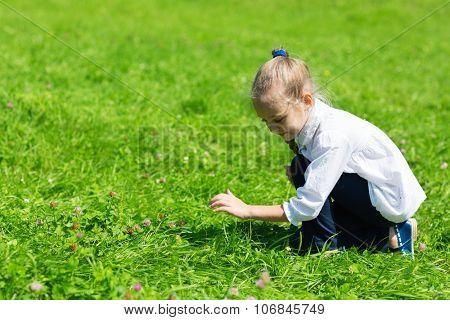 Girl catching a grasshopper in the grass
