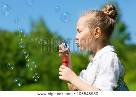 Happy girl blowing soap bubbles outdoors.