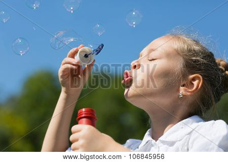 Charming girl blowing soap bubbles outdoors.