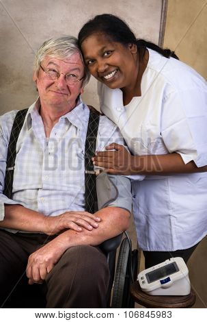 Nurse measuring blood pressure of an elderly man in a wheelchair