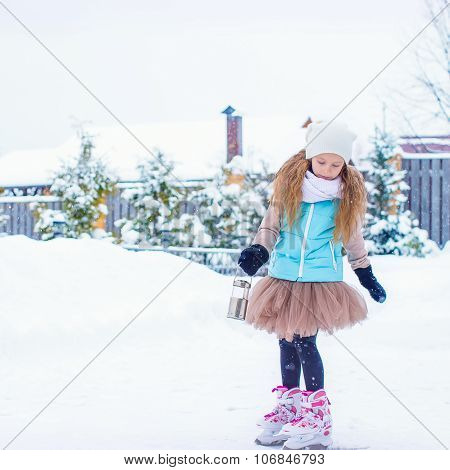 Adorable fashion little girl skating on the ice rink outdoors